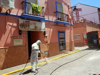 An Algeciras city worker disinfects the outside of a hostel following a coronavirus outbreak.