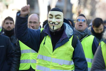 A taxi driver wearing a Guy Fawkes mask and a yellow vest during a strike in Barcelona.