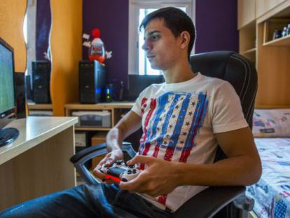 José Luis Flores plays on his PlayStation in his room.