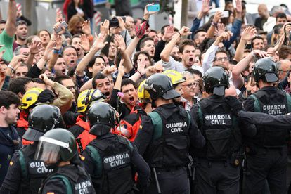 Firefighters place themselves between protesters and Civil Guard riot officers outside a polling station in San Julià de Ramis, Catalonia.