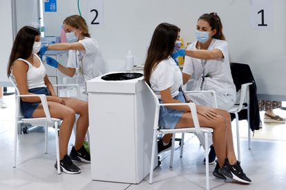 Two teenagers are vaccinated against Covid-19 in Madrid last Wednesday.
