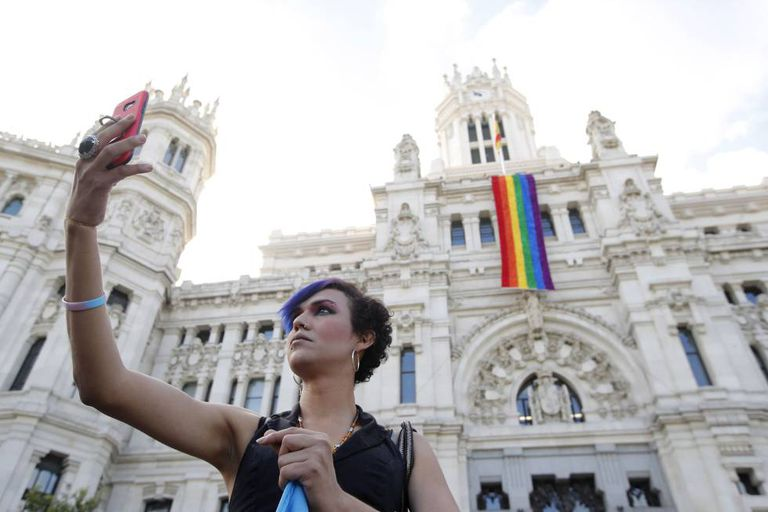 The gay pride flag hangs from Madrid City Hall.