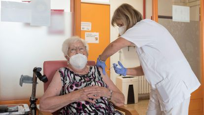 A resident of a senior home is given a third shot of a Covid-19 vaccine.