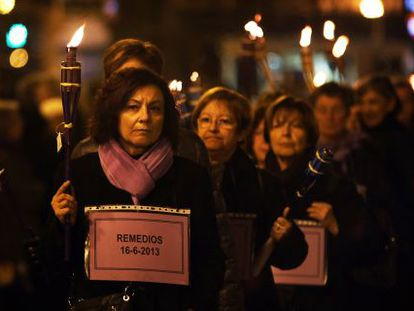 A group of women carries 77 torches in memory of the victims of gender violence in Spain last year.