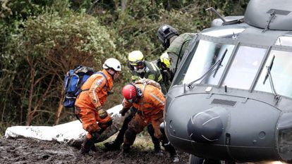 Rescue workers removing a body from the crash site.