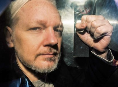 Julian Assange gesturing from the window of a prison van as he was driven into Southwark Crown Court in London on May 1, 2019 after Ecuador withdrew his asylum status.