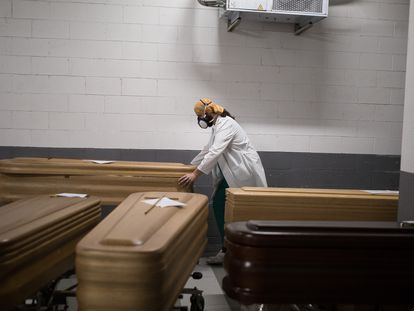 Funeral worker moving a coffin to the basement of the Sancho de Ávila funeral home in Barcelona.