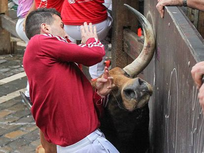 A runner is hit by a bull during Sunday's Sanfermines.