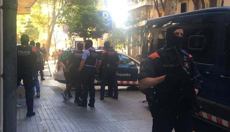 Police escort a suspect on Tamarit street in Barcelona.