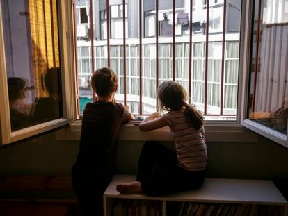 Two siblings look out their bedroom window during the lockdown in Madrid.