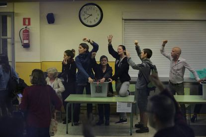 Volunteers grab a ballot box with their fists in the air at the Ramon Llull school in Barcelona.