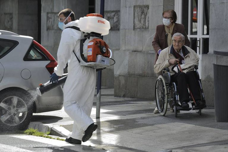 An elderly couple observes a man disinfecting the streets of Vitoria in Spain's Basque Country on Monday.