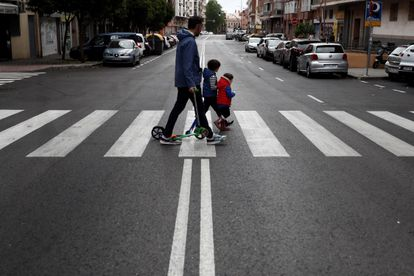 Two children cross a road in Madrid on Sunday.