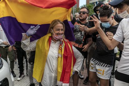 An anti-government protester stands in front of anti-fascists waving Spain's Republican flag in Alcorcón.