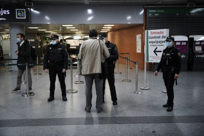 National Police officers checking passenger ID at Atocha railway station in Madrid.