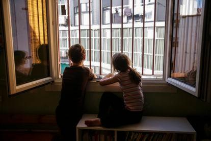 Two siblings look out their bedroom window during the lockdown in Madrid.