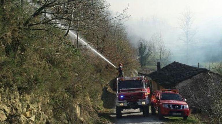 Firefighters try to put out a blaze near Vega de Pas, Cantabria.