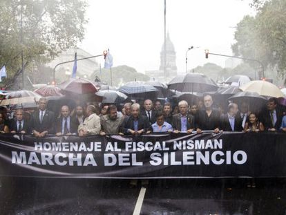 People march under heavy rain showers in Buenos Aires on Wednesday.