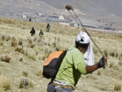 A protestor slings a rock at police at the Tintaya mine.