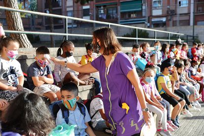 A teacher takes children's temperature at Rafael Casanova school in  Badalona, in Catalonia.