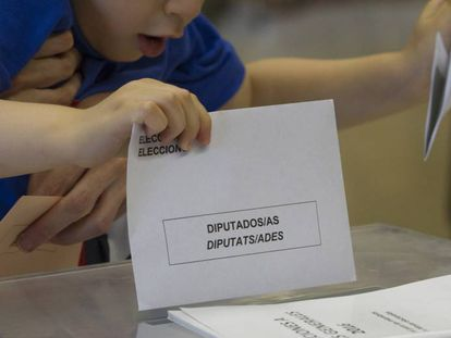 A young boy places a voting slip in Barcelona.