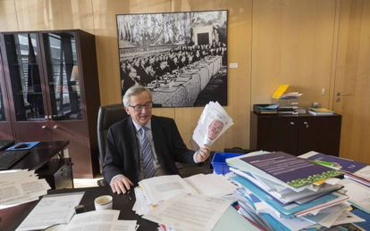 Jean-Claude Juncker holds up a copy of EL PAÍS inside his Brussels office.