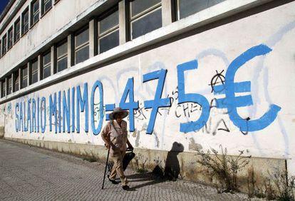 "A mural reading ""Medium wage = €475."""