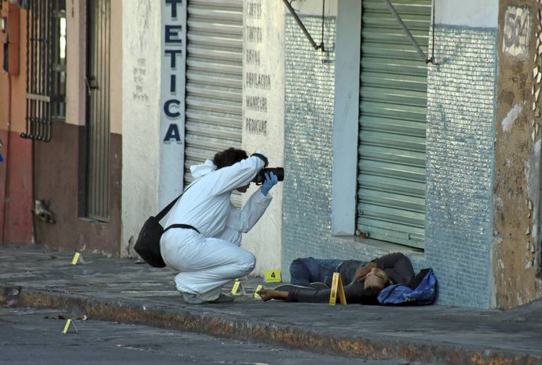 A forensics photographer at a crime scene in Cuernavaca, Morelos.