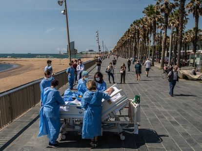 Staff at the Mar de Barcelona hospital take a Covid-19 patient to the seaside as part of a program to humanize intensive care treatment.