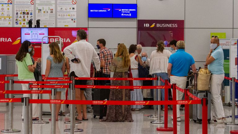 Passengers in Palma de Mallorca airport in the Balearic Islands line up for a flight to the UK on Sunday.
