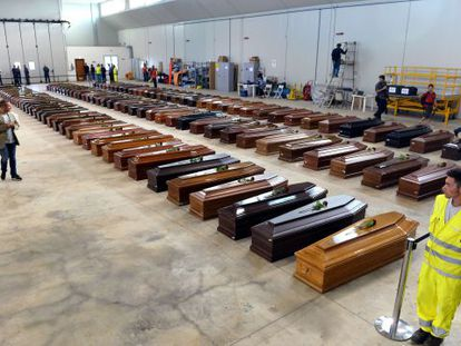 Coffins of dead migrants are lined up in a hangar of Lampedusa airport.