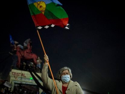A woman with a Mapuche flag celebrates the results of the referendum to write a new Constitution.