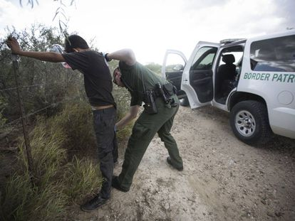 A border control agent searches an undocumented immigrant in Roma, Texas.