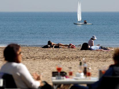 Beachgoers enjoy the unseasonably warm weather in Valencia.