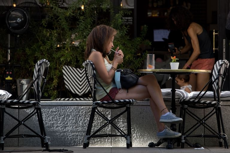A woman smokes at an outdoor cafe in Madrid.