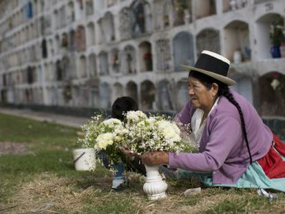 A woman lays flowers on the grave of a relative.