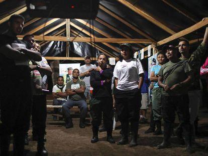 FARC guerrillas watch TV at a camp.