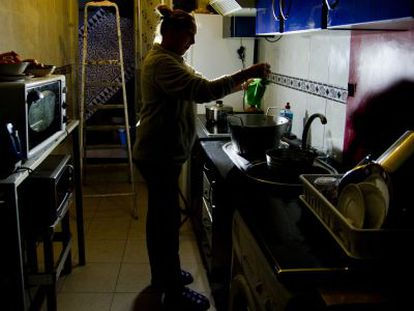 A woman works in her kitchen despite water and power cuts.