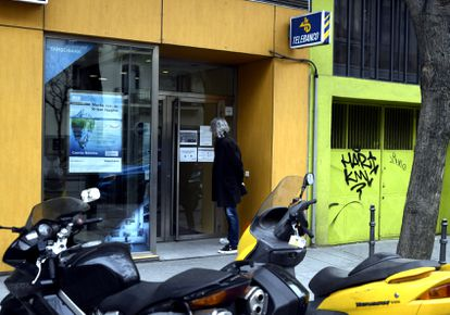 A man reads the coronavirus measures on signs at a branch of Targo Bank in Madrid.