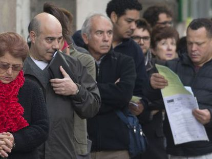 Jobseekers wait in line outside a Madrid unemployment office.