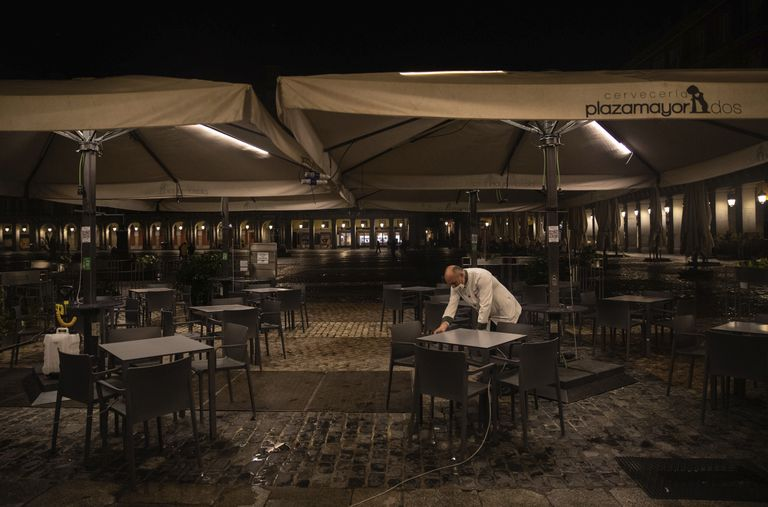 A waiter closes the terrace of a bar in Plaza Mayor, Madrid on Friday.