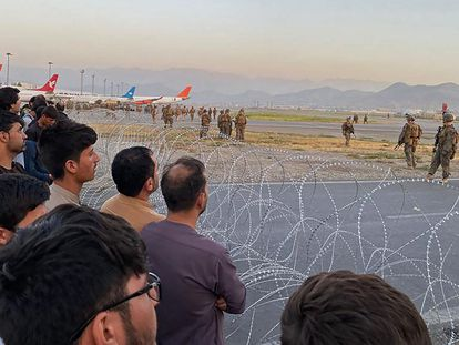 Afghans gather outside Kabul airport on Monday while US soldiers stand guard.