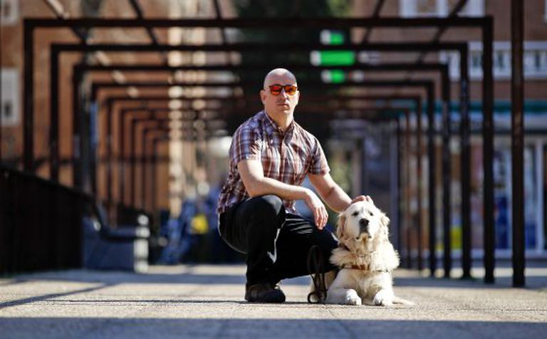 Raúl Fernández with his guide dog, close to his home in Madrid.