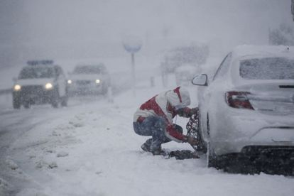 A man fits snow chains on his car in Lugo province.