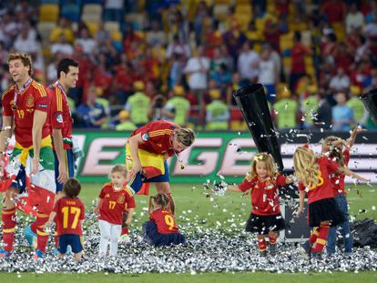 Spain players Llorente, Busquets and Torres (l to r) in Kiev after the final together with various squad-connected children.