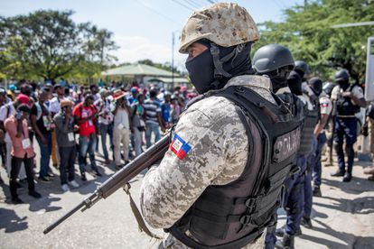 An armed police officer watches over a protest by journalist in Port-au-Prince.