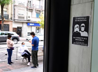 "Residents in the Madrid district of Puente de Vallecas. The sign reads: ""Face masks mandatory."""