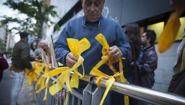 A man removes yellow ribbons from a public space in Catalonia.