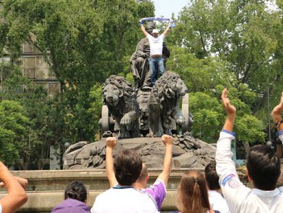 A fan of the Spanish side celebrates atop the fountain.