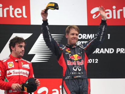 Sebastian Vettel (R) of Red Bull Racing celebrates on the podium after he won the India Grand Prix ahead of Fernando Alonso (L).